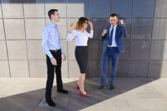Tre belle genti energetiche ridono, si rallegrano il successo, sorridente Fotografia Stock Libera da Diritti