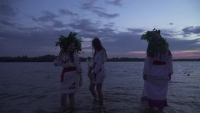 Tre belle ragazze camminano intorno nei cerchi nell'acqua video d archivio