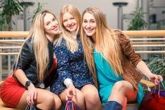 Tre belle ragazze con i sacchetti della spesa Fotografie Stock