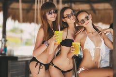 Tre belle ragazze in una barra sulla spiaggia Fotografia Stock