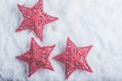 Tre belle stelle rosse d'annata magiche su un fondo bianco della neve Concetto di Natale e di inverno Fotografia Stock