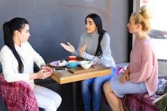 Tre berättar härligt kvinnligt leende i kafé, samtal, hemligheter, äter, D royaltyfri fotografi