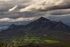 tre bergmaxima runt om den gröna dalen Arkivbild