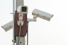 Tre bevakningsäkerhetskameror på vit himmelbakgrund Royaltyfri Fotografi