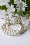 Tre bianchi e braccialetti rosa e fiori bianchi Fotografia Stock