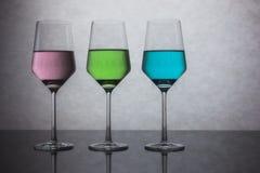 Tre bicchieri d'acqua colorati Fotografie Stock