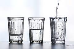 Tre bicchieri d'acqua con spruzzano Fotografie Stock