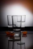 Tre bicchieri d'acqua su fondo arancio con il mandarino Fotografia Stock