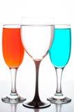 Tre bicchieri di vino con i liquidi colorati Immagine Stock