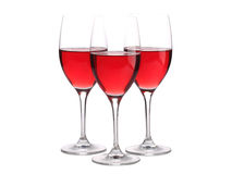 Tre bicchieri di vino con un certo vino isolato su bianco Immagine Stock Libera da Diritti
