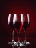 Tre bicchieri di vino con un certo vino su rosso Fotografia Stock Libera da Diritti