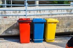Tre bidoni della spazzatura variopinti per la separazione dell'immondizia Fotografia Stock
