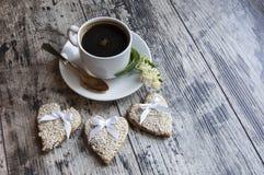 Tre biscotti di nozze hanno decorato il sesamo bianco con una tazza di caffè. Retro stile. Fotografia Stock Libera da Diritti