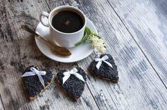 Tre biscotti di nozze hanno decorato il sesamo nero con una tazza di caffè. Retro stile. Immagine Stock
