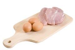 Tre bistecche del porco ed uova marroni sulla scheda di taglio Immagini Stock