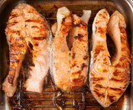 Tre bistecche di color salmone fritte sulla pentola della griglia Fotografia Stock