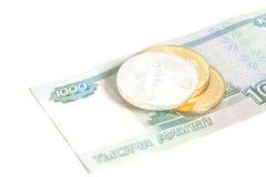 Tre Bitcoin su mille rubli russe di banconote Immagini Stock