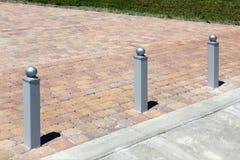Tre bitte del metallo attraverso la pavimentazione delle mattonelle Fotografia Stock