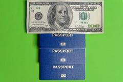 Tre blåa biometric pass med hundra dollarvalör arkivbild