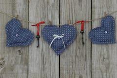 Tre blåa hjärtor som hänger på klädstreck Royaltyfri Foto
