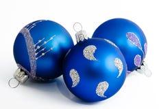 Tre blåa julbollar som isoleras på en vit Royaltyfri Bild