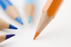 Tre blåa och för en apelsin blyertspennor Arkivfoto