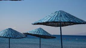 Tre blåa slags solskydd på stranden av Bodrum med det aegean havet på th Arkivfoton