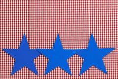 Tre blåa stjärnor gränsar röd rutig bakgrund (för gingham) Arkivfoto