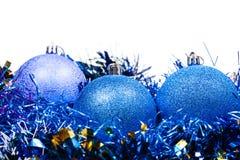 Tre blåa isolerade julstruntsaker och glitter Arkivfoto