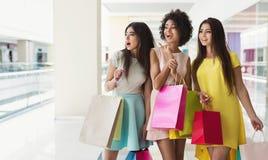 Tre blandras- flickor som tillsammans shoppar i galleria royaltyfria foton