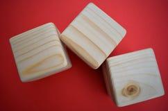 Tre blocchi di legno su fondo rosso Fotografia Stock Libera da Diritti