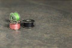 Tre bobine della macchina per cucire con il filo variopinto Immagine Stock