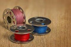 Tre bobine della macchina per cucire con il filo variopinto II Fotografia Stock