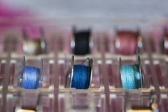 Tre bobine della macchina per cucire con il filo variopinto in un supporto di plastica Immagini Stock