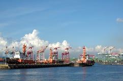 Tre bogserbåtar i en behållareport Royaltyfria Bilder