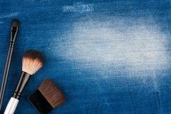 Tre borstar för makeup som ligger på jeans Royaltyfri Bild