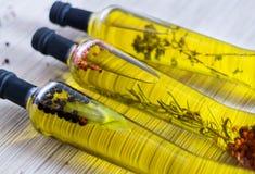 Tre bottes di olio d'oliva con gli spieces, rosmarini, pepe, orega Immagini Stock