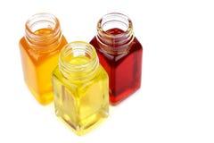 Tre bottiglie con gli oli isolati su bianco Immagini Stock