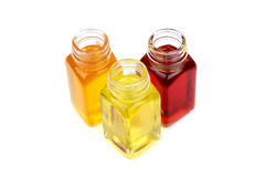 Tre bottiglie con gli oli su fondo bianco Fotografie Stock