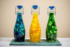 Tre bottiglie con la limonata luminosa della frutta di colore, stile della barra Immagine Stock