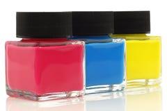 Tre bottiglie con la vernice di colori primari Immagini Stock