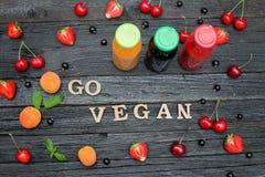 Tre bottiglie con succo, frutta e l'iscrizione vanno vegano nero Immagine Stock
