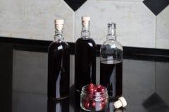 Tre bottiglie del vino rosso della ciliegia Fotografie Stock