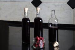 Tre bottiglie del vino rosso della ciliegia Immagini Stock