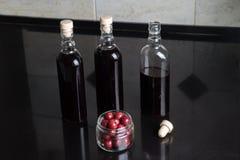 Tre bottiglie del vino rosso della ciliegia Fotografia Stock