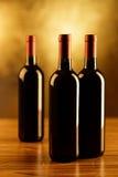 Tre bottiglie del vino rosso sulla tavola di legno e sul fondo dorato Fotografia Stock