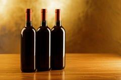 Tre bottiglie del vino rosso sulla tavola di legno e sul fondo dorato Immagini Stock Libere da Diritti