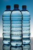 Tre bottiglie di acqua sul Bakcground blu Immagine Stock Libera da Diritti