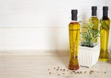 Tre bottiglie di olio d'oliva con le spezie Immagini Stock