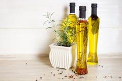 Tre bottiglie di olio d'oliva con le spezie Fotografie Stock